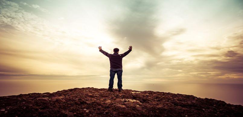 Man standing under orange sky with hands up