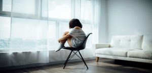 Woman sitting on chair depressed looking out window