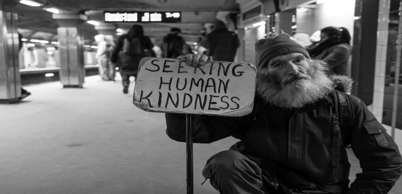 Homeless man holding a sign asking for kindness